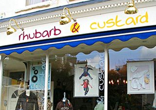 Retail shop signs fascia with awning and brass overhead lighting